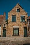 Ceglana fasada starzy domy i drzwi z niebieskim niebem, w pustej ulicie Bruges Zdjęcia Stock