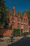 Ceglany dom i kobieta jedzie bicykl w Bruges Zdjęcie Stock