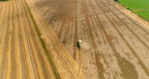 A ceifeira de liga recolhe a colheita do trigo filme