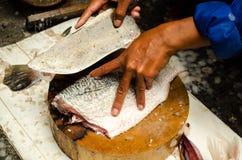 Ceignant d'un bandeau un poisson coupé sur la planche à découper Marché de poissons à Hong Kong Photo stock
