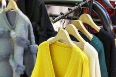 Ceilão na moda amarelo e outras camisetas feitas malha de lã da cor que penduram em ganchos na loja, close-up imagem de stock royalty free