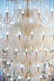 Ceiling chandelier of classic vintage style shape. Made of crystal and glass with candle shaped lamps stock photo