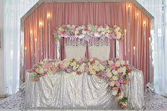Ceiling Decor with tulle and eclectic chandeliers. Ornament of beautiful colorful flowers of rose and peony pink purple white. skaterd and silver on the table Stock Photo