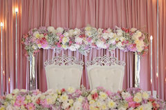 Ceiling Decor with tulle and eclectic chandeliers. Ornament of beautiful colorful flowers of rose and peony pink purple white. skaterd and silver on the table Royalty Free Stock Photos