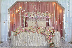 Ceiling Decor with tulle and eclectic chandeliers. Ornament of beautiful colorful flowers of rose and peony pink purple white. skaterd and silver on the table Royalty Free Stock Image