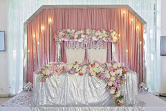 Ceiling Decor with tulle and eclectic chandeliers. Ornament of beautiful colorful flowers of rose and peony pink purple white. skaterd and silver on the table Stock Image