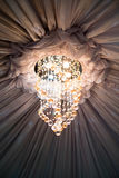 Ceiling drape and sparkling chandelier near the center area Royalty Free Stock Photos