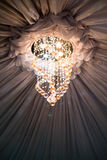 Ceiling drape with sparkling chandelier Stock Images