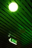 Ceiling and exit sign. A picture of a ceiling made up of metal bars with lamp light and emergency exit sign on it stock photos