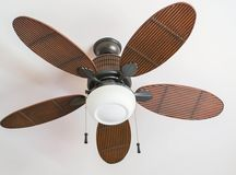 Ceiling fan. Brown tropical wicker fan on a white ceiling with lamp Stock Images