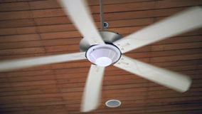 Ceiling fan spinning in slow motion stock footage