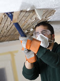 Ceiling Fix. Man scraping plaster from ceiling lathe. renovation Royalty Free Stock Image