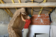 Ceiling insulation. A worker who insert the ceiling insulation Stock Photo