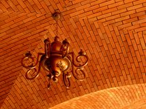 Ceiling Lamp. A bronze color lamp hanging from a ceiling made of bricks Stock Photos