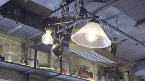 Vintage industrial lamp. Ceiling lamp decor home or shop bright in orange light. Beautiful antique retro vintage edison light bulbs garland in loft interior on stock video