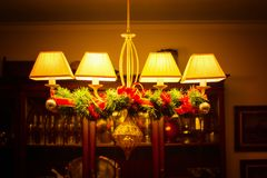 Christmas decorations in a ceiling lamp. Ceiling lamp with some christmas decorations on a cozy environment Royalty Free Stock Photography