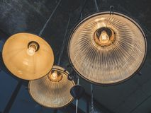 Ceiling lamps. A group of hanging lights or ceiling lamps on cement texture background in loft style cafe stock image