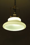 Ceiling light. Light hanging from ceiling with the light on in a dark room Royalty Free Stock Photos