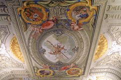 The ceiling painting in an ancient Spanish castle. A picture on the ceiling. Coat of arms. Molded ornaments. Painting for the rich stock images