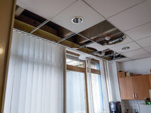 Ceiling panels damaged and collapsed by water. Rainwater leakage damage stock image