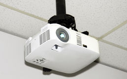 Ceiling projector. Close-up of a multi-media projector attached to the acoustic ceiling tiles of a small office Royalty Free Stock Photos