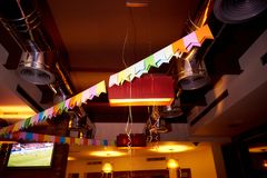 The ceiling of the pub is decorated with colorful flags and ribbons royalty free stock photos