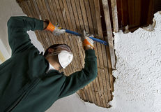 Ceiling Repair. View from below. man removing plaster lathe from ceiling Royalty Free Stock Photography