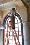 Ceiling Restoration. A woman on a ladder restoring a ceiling stock photos