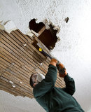 Ceiling Take Down. Vertical shot from below of a man pulling down plaster ceiling lathe with a crowbar. large hole in ceiling royalty free stock photos