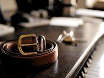 Ceinture en cuir de Brown avec la boucle en bronze d'or sur le bureau en bois foncé photo libre de droits