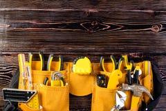 Ceinture jaune en cuir d'outil avec l'outillage de construction sur le bois brun photos libres de droits