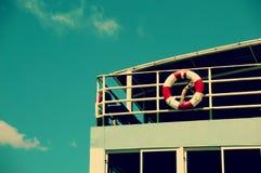 Ceinture orange en plastique d'économie par la barrière de balustrade du ferry Image libre de droits