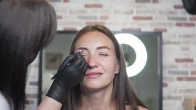 Cejas de pintura en un salón de belleza El cosmetólogo da forma a las cejas y las pinta en un color oscuro almacen de video