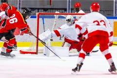 Cel! Hokeja na lodzie gracz strzela krążek hokojowego w sieci obraz royalty free