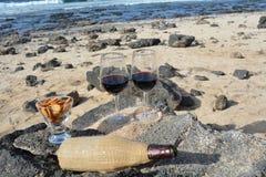 Celebração com dois vidros do vinho tinto na praia tropical agradável Imagem de Stock