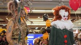 Celebração de Dia das Bruxas, mulher em um suporte do traje de Gorgon perto do palhaço com os balões vermelhos no close-up da cen filme
