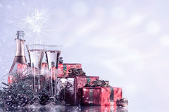 Celebração do ano novo e do Natal Champagne, dois vidros de vinho, fogos-de-artifício e presentes no fundo do feriado piscar Foto de Stock