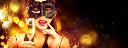Celebração do feriado do Natal e do ano novo Mulher da beleza que comemora com champanhe, máscara vestindo do carnaval Champagne  imagem de stock royalty free