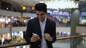 Celebração do homem de negócios seu sucesso ao olhar um telefone celular vídeos de arquivo