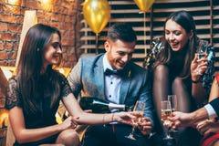 Celebração do partido Amigos que derramam o champanhe e que têm o divertimento fotografia de stock