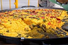 Celebração ou fest público na Espanha Grande frigideira do fla com paella cozinhado Venda aos convidados imagens de stock