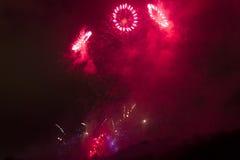 Celebração vermelho-cor-de-rosa brilhante surpreendente do fogo de artifício dos anéis do ano novo 2015 em Praga sobre a escultur Imagem de Stock Royalty Free
