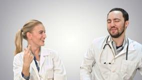 Celebración, baile y cantando médicos de los colegas en el fondo blanco metrajes
