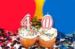 Celebración con los globos, el confeti, y la magdalena Imagenes de archivo