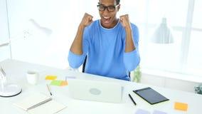 Celebración de éxito mientras que trabaja en el ordenador portátil, entusiasmo almacen de video