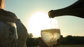 celebración de éxito y de la victoria Vino espumoso Pour de la botella en las copas de vino transparentes contra una puesta del s almacen de metraje de vídeo