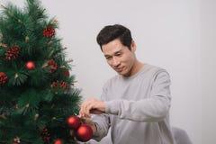 Celebración de Año Nuevo Hombre asiático que hace una pausa el nuevo árbol de navidad a Fotos de archivo libres de regalías