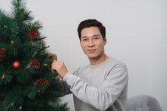 Celebración de Año Nuevo Hombre asiático que hace una pausa el nuevo árbol de navidad a Foto de archivo libre de regalías