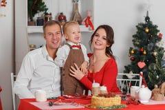 Celebración de familia feliz del Año Nuevo La madre, el padre y el pequeño hijo sentándose en la tabla Foto de archivo