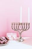Celebración de Jánuca, el primer día Palmatoria, anillos de espuma fritos y regalo, en el fondo blanco y rosado Imagenes de archivo